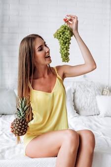 Девушка с кокосом в руке смотрит на виноград