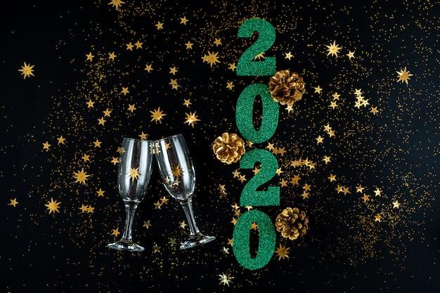 Зеленые цифры нового года, кубки, золотые шишки и золотые звезды на праздничном черном фоне
