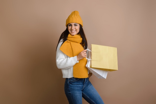 ショッピングバッグ、大きな割引のシーズン、コピースペースと暖かい服装で幸せな女の子