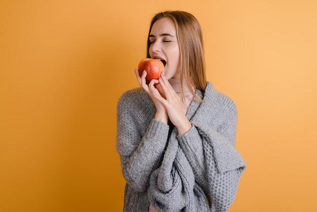 スタジオで笑顔のかわいい若い女性。リンゴを食べる