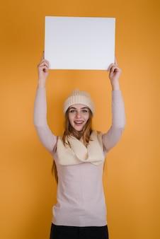 Красивая, улыбчивая девушка подняла над головой чистый лист бумаги