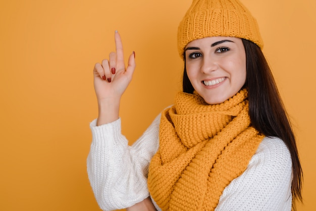 指で身振りで示す若い幸せな女性は、良いアイデアとインスピレーションの動機に達すると興奮しています。