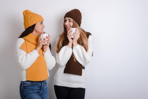 女の子はマグカップを保持し、白い背景の上の冬の服でお互いを見て
