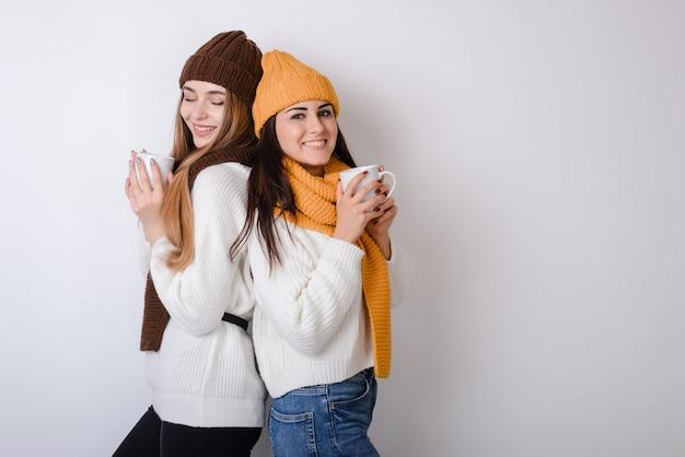 Две подружки стоят спиной друг к другу и держат в руках кружки.