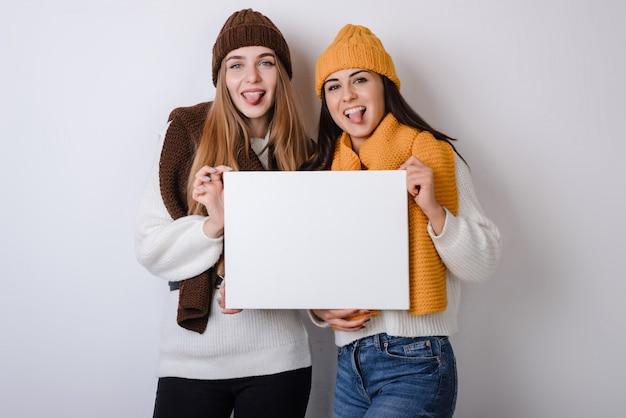 Две подружки в шляпах держат белый плакат