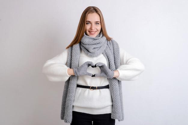 Девушка делает сердце руками зимой
