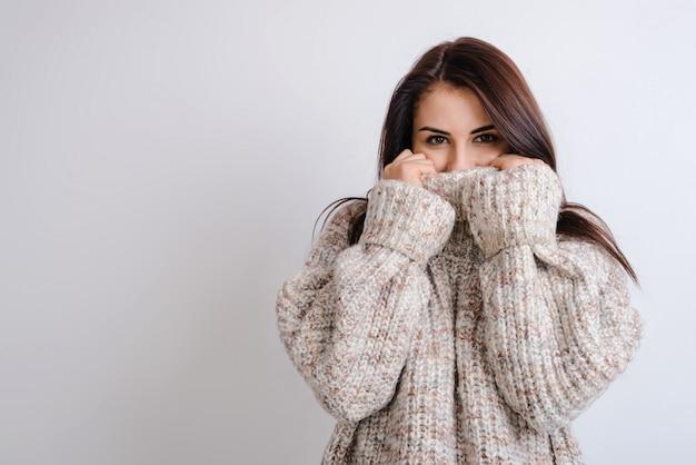 Красивая девушка закрывает лицо свитером
