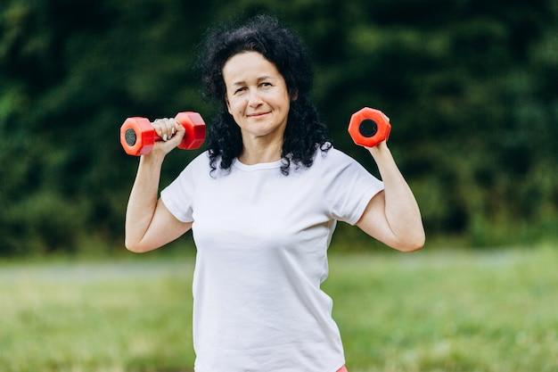 中年の女性が彼女の手でダンベルを保持していると屋外運動をしています。スポーツ
