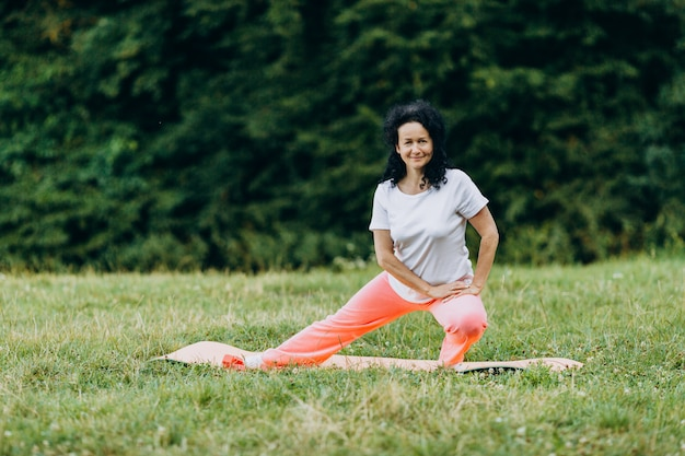中年の女性が屋外で運動し、彼女の足を伸ばします。スポーツ