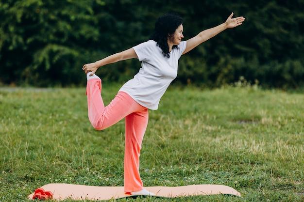 中年の女性が彼女の足を屋外に保持するヨガのポーズを行います。スポーツ