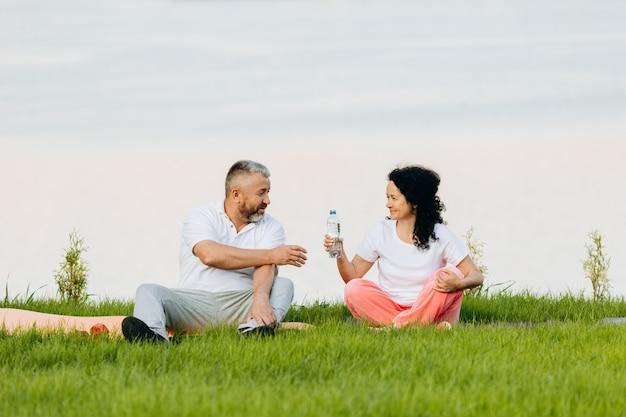 幸せな年配の女性と座っていると休憩の男。女性は男性に水を与えます。