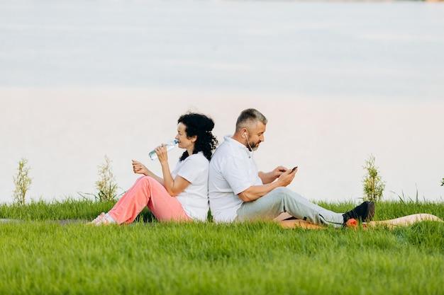 年配の女性と草の上に座っている年配の男性。電話を探しているイヤホンで水と男を飲む女性。
