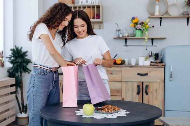 Красивые девушки подружки рассматривают свои покупки дома