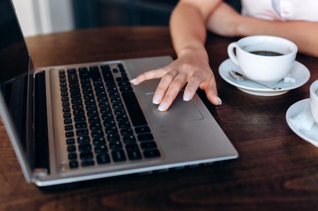 カフェでラップトップに取り組んでいる女の子