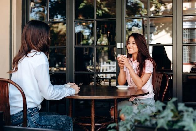 Довольно милая брюнетка разговаривает друг с другом сидя за столом