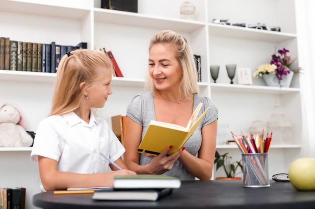 愛情深い母親は彼女の小さな娘に本を示しています