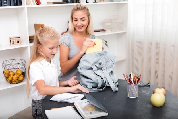 宿題をしているかわいい女の子は、母親と一緒にバックパックを作ります