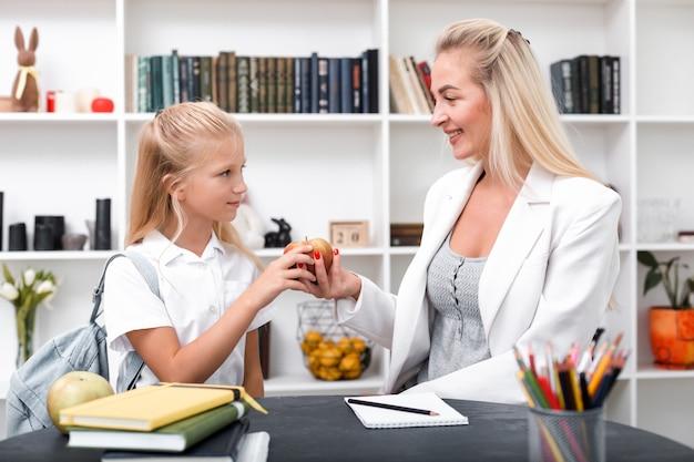 Молодая, улыбающаяся мама дает дочери яблоко в школу