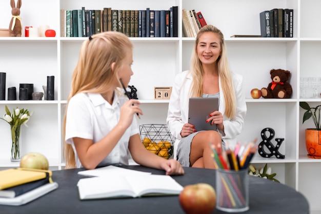 かわいい、笑顔の女の子はレッスンを学び、彼女のお母さんに何かを尋ねています