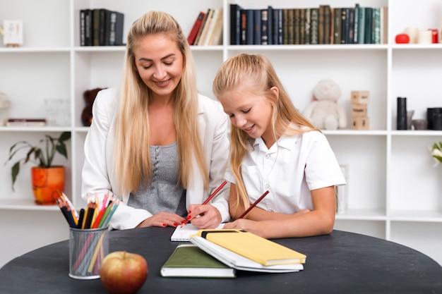 愛情深い母親は彼女の小さな娘がレッスンを学ぶのを手伝います