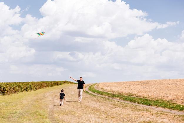 Папа и сын гуляют на улице, запускают змея на природе
