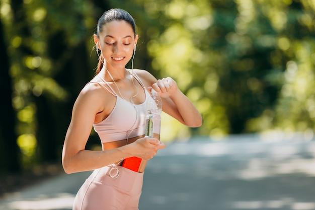 水のボトルを保持している女の子と屋外のイヤホンで音楽を聴く