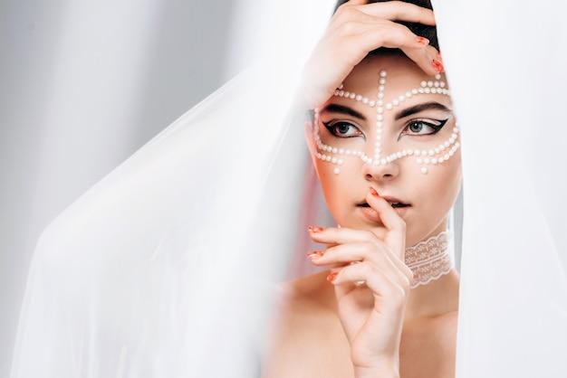 Модная женщина смотрит под вуалью, касается ее лица руками