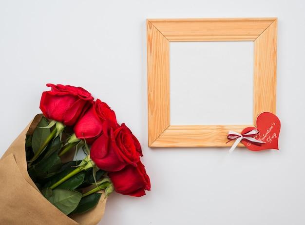 Красные, красивые розы и деревянная рамка лежат на белой поверхности