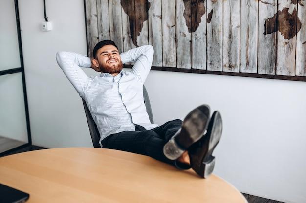 Привлекательный парень с бородой кладет руки за голову, ставит ноги на стол и отдыхает.