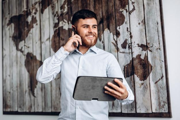 電話で話していると、タブレット上の重要な文書を見ているハンサムな忙しいビジネスマン。