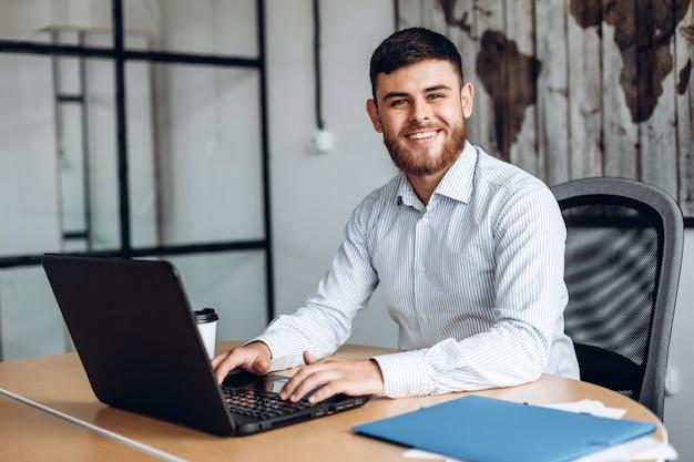 笑みを浮かべて、ひげを生やした男のオフィスのコンピューターで作業