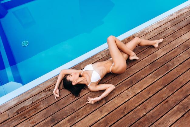 Стройная девушка отдыхает возле бассейна