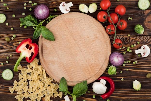 チェリートマトに囲まれ、グリーン、パスタ、コショウを添えた丸い木の板の近くのイタリア製品