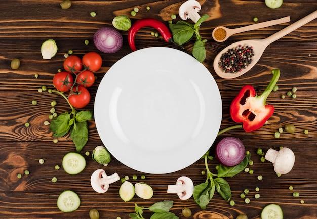 木製のテーブルの上には、イタリア製品とスパイスに囲まれたプレートがあります