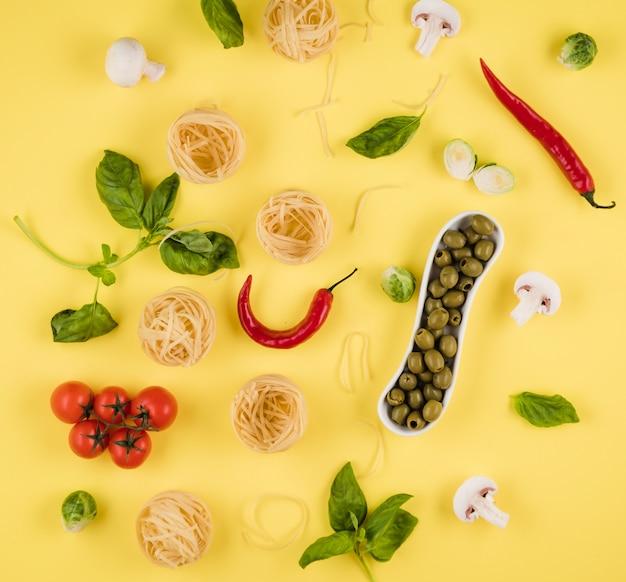 上面図、黄色の背景にレイアウトされたおいしい食材。イタリア料理の調理の概念