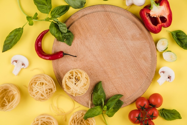 チェリートマトとグリーン、ペースト、コショウに囲まれた丸い木の板の近くのイタリア製品