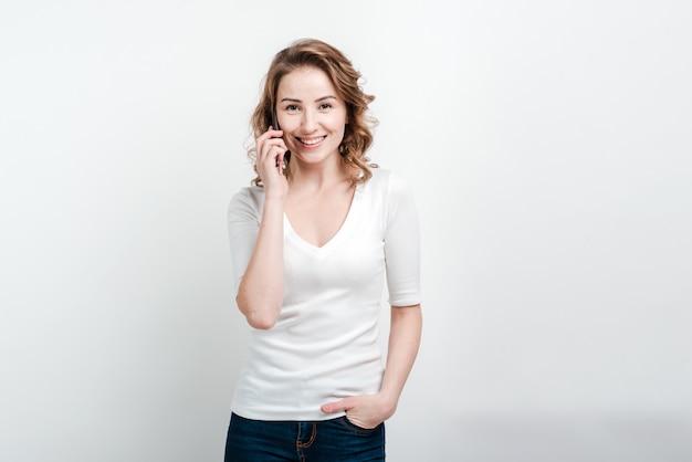 携帯電話で話していると笑顔、分離された美しい女性