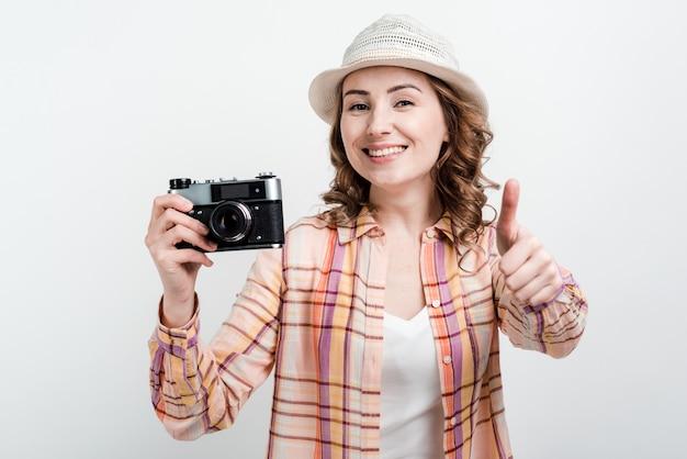 帽子のきれいな女性と手でレトロカメラは親指を現して彼女の仕事に満足しています。