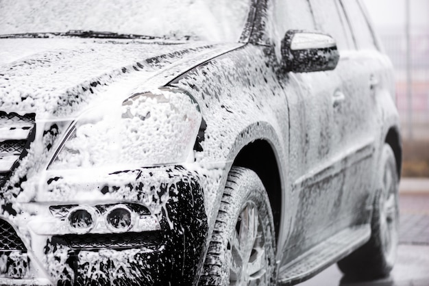 屋外に立っている石鹸で黒い車。正面図
