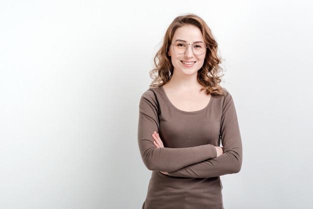 Улыбающиеся женщина в очках стоит со скрещенными руками. изолированные