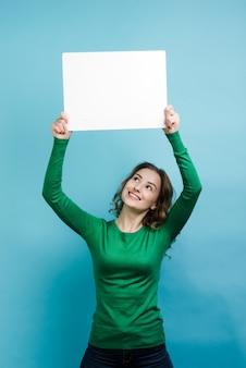Женщина держит пустой белый плакат