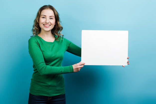 Улыбающиеся женщина, держащая пустой белый плакат