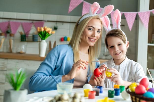Веселая, веселая, радостная мама учит, тренирует маленького сына рисовать, рисовать, украшать пасхальные яйца, вместе носить кроличьи уши, готовится к пасхе