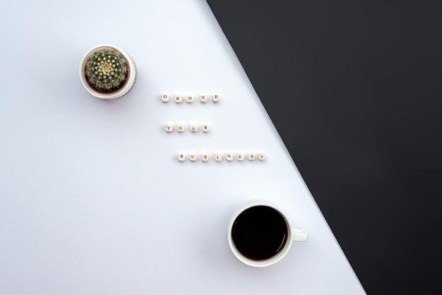 碑文は、白と黒の机の上にあなたのビジネスをサボテンとコーヒーカップ