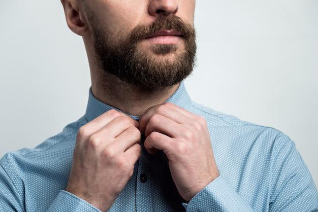 男性の腕のクローズアップは、シャツのボタンを締めます。