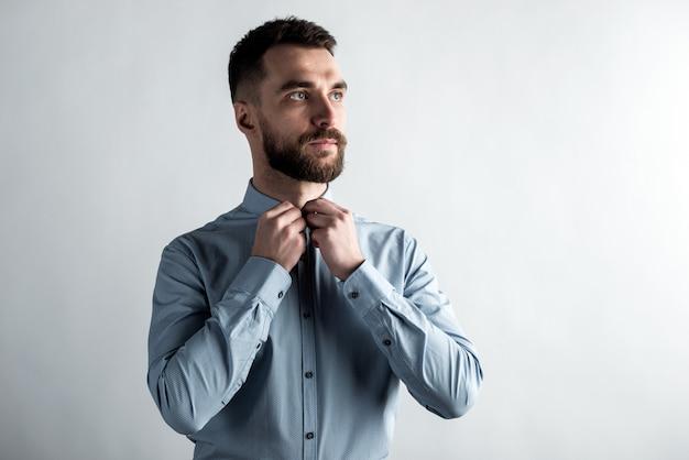 真剣に男の肖像は、シャツのボタンを締めます。