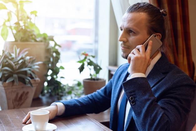 Человек, пить кофе в кафе-баре с помощью мобильного телефона. молодой модный человек во время обеда