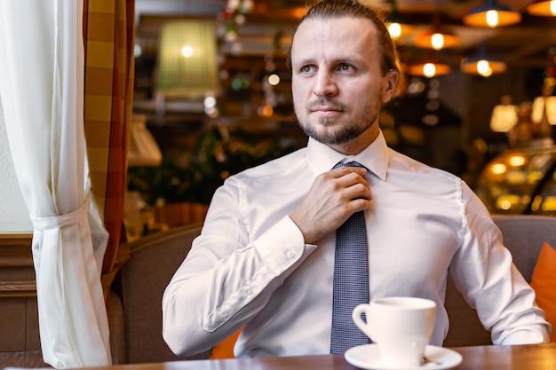 Серьезный человек смотрит в сторону, сидя в ресторане в помещении, одетый в белую рубашку и поправляющий галстук