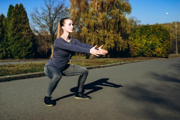 スポーツウェアとヘッドフォンを屋外でトレーニングしながら腹筋運動をしている女の子。