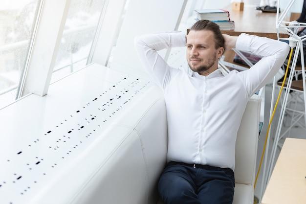 Мечтательный человек, сидящий в позе расслабиться на диване у окна в белом современном интерьере.
